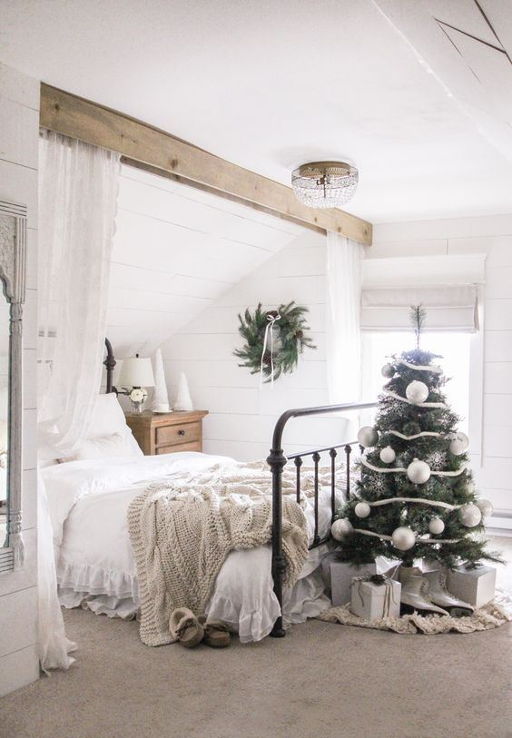 a small Christmas tree with white and silver ornaments, gift boxes and an evergreen wreath with pinecones for holiday decor