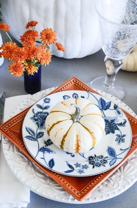a stack of white, orange and blue and white plates and a blue vase with orange blooms for a chic Thanksgiving table