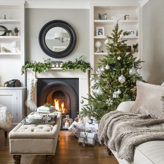 a stylish Christmas tree with silver ornaments, a stocking and a greeneyr garland with pinecones on the mantel