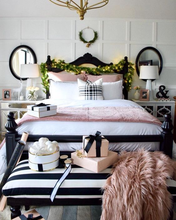 a super elegant Christmas bedroom with pearly ornaments, a greenery and light garland, a mini wreath with bells