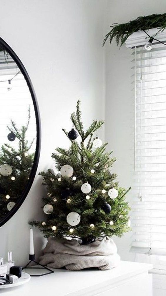 a tabletop Christmas tree with lights and black and white ornaments is a perfect monochromatic piece