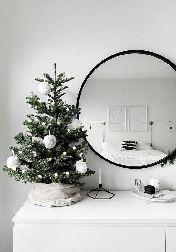 a tabletop Christmas tree with lights and white pompom ornaments is a stylish and minimal idea