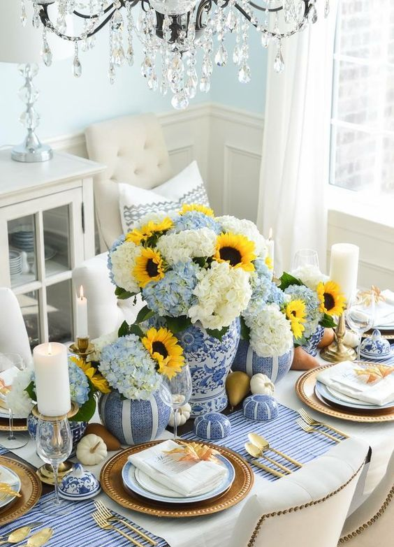 a traditional Thanksgiving table setting with a blue striped tablecloth, blue vases and faux pumpkins looks very stylish
