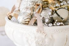 a vintage white bowl with silver and gold glitter Christmas ornaments and bells plus crystals and ribbons as a refined holiday centerpiece