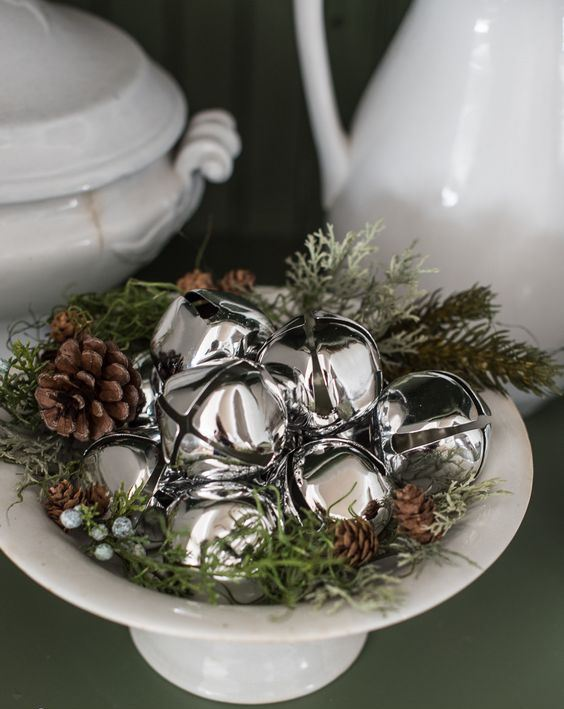 a white bowl with grass, berries, pinecones and silver bells is a chic and cozy natural Christmas decoration to rock