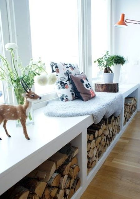 a windowsill bench with storage allows storing there some firewood for your fireplace and add coziness to the room