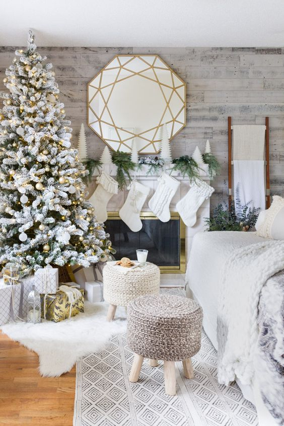 a winter wonderland living room with a flocked Christmas tree with white and gold ornaments, white stockings, mini Christmas trees and fir branches