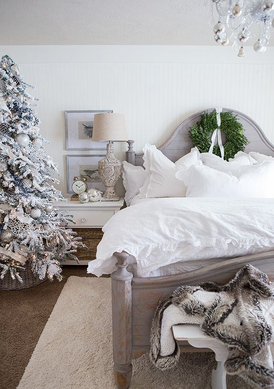 an elegant farmhouse Christmas bedroom with a snowy tree with lights and ornaments, faux fur, a greenery wreath and silver ornaments