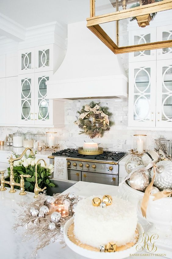 an evergreen Christmas wreath with metallic ornaments, metallic ornaments in bowls, silver ornaments wreaths and candles