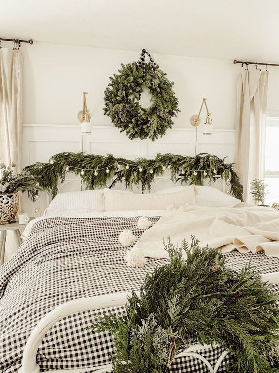 an evergreen wreath with pinecones, evergreen garlands with bulbs and plaid bedding for a farmhouse Christmas look