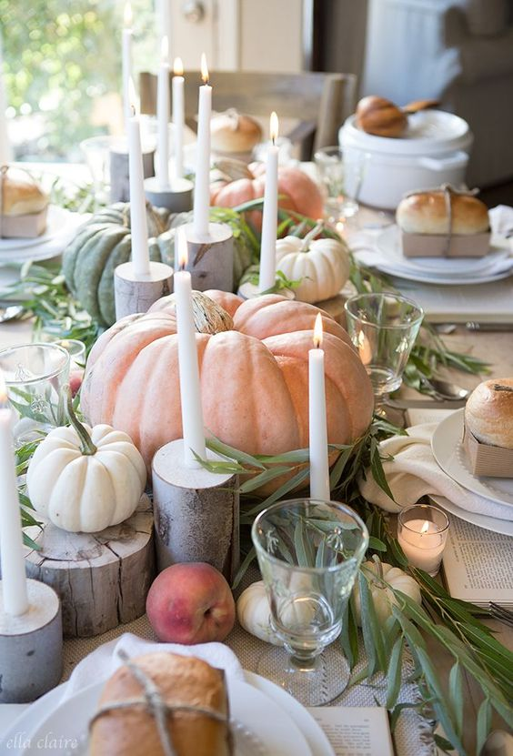 beautiful whitewashed pumpkins and peaches, greenery, white candles and tree stumps and candles around for Thanksgiving