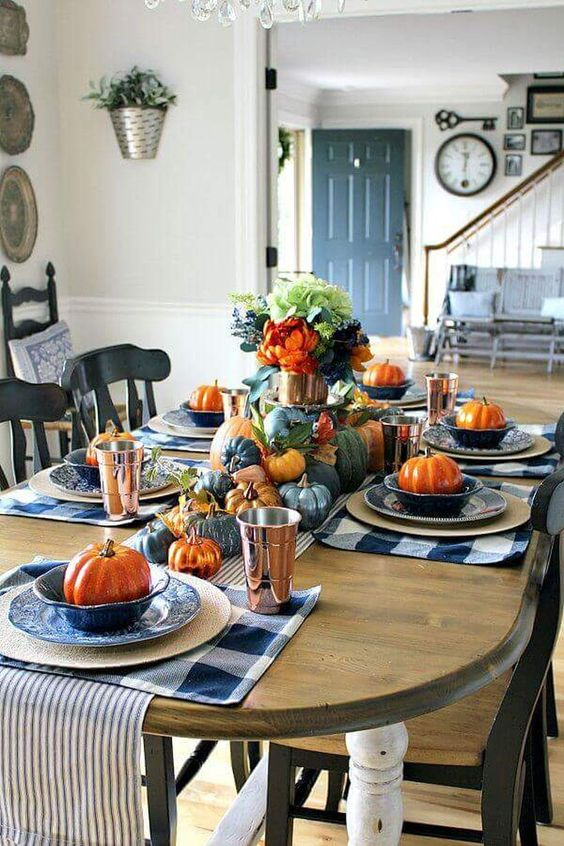blue and white plaid placemats, blue and orange pumpkins, blue flwoers and striped napkins for Thanksgiving