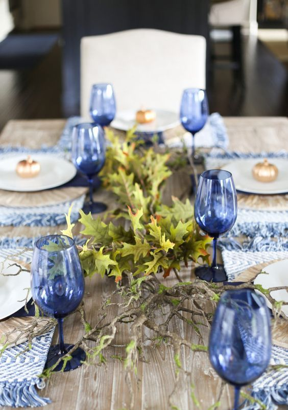 blue woven placemats with fringe and blue glasses will give a new and frehs look to your Thanksgiving table
