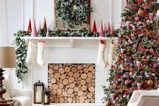bright and bold Christmas living room decor with red mini trees, a greenery garland, a greenery and berry wreath, a Christmas tree with bold red ornaments and beads