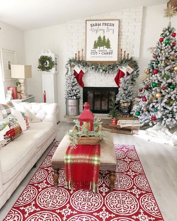 bright and fun Christmas decor with a flocked tree with gold, green and red ornaments, plaid pillows and a runner, red stockings, a flocked garland and flocked mini trees