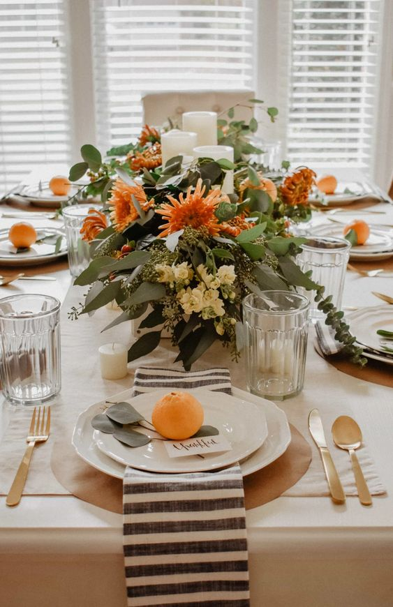 bright fall blooms with greenery and candles paired with bright citrus on the place settings are amazing for a modern Thanksgiving table