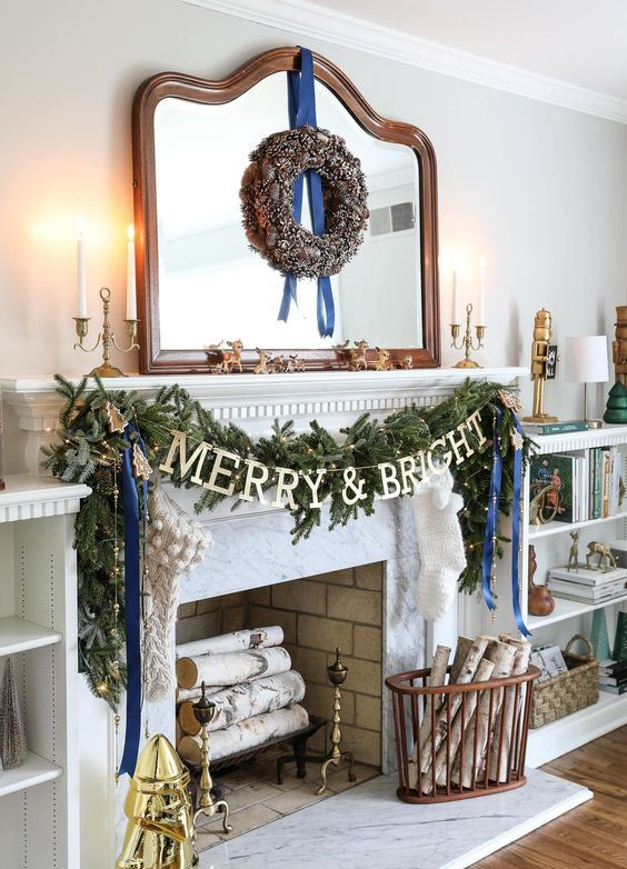 chic Christmas decor with a pinecone wreath, a fir garland with lights and blue ribbons, branches in a basket