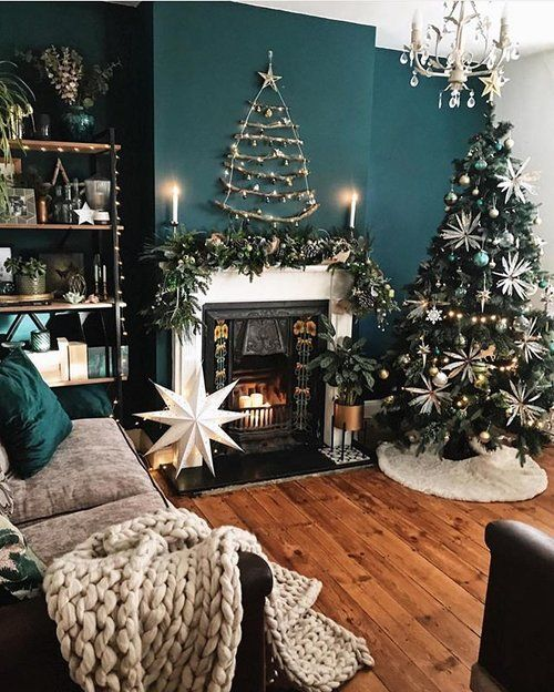 chic and glam Christmas decor with a tree decorated wiht white and grene ornaments a fir branch garland and a stick tree on the wall