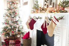chic rustic Christmas decor with red and neutral stockings, mini trees, fir garland with berries, candles and a Christmas tree with mesh ribbons and white and red ornaments