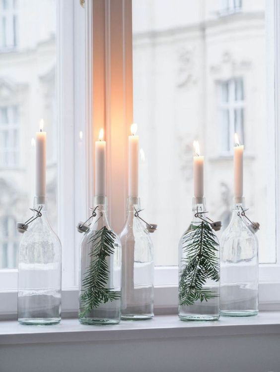 clear bottles with evergreens and white candles are nice to decorate your space in minimalist style