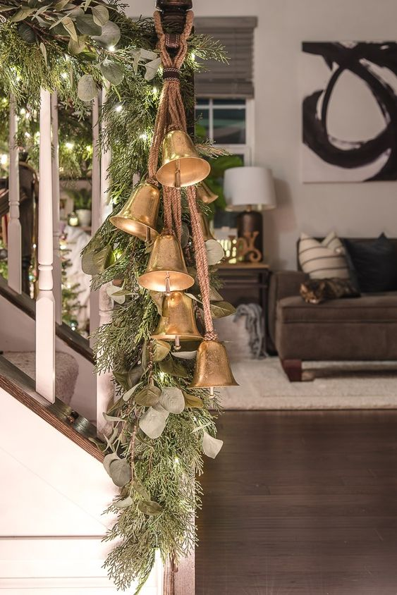 decorate the railing with foliage, fir branches, lights and vintage bells to make your space look very holiday-like