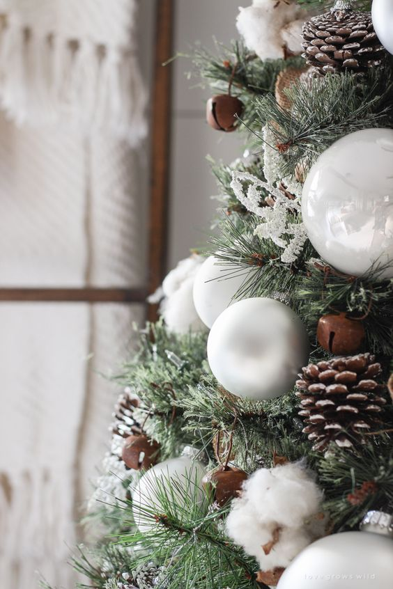 decorate your Christmas tree with pinecones, cotton, bells and white ornaments to give it a cozy rustic look