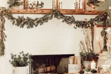 elegant rustic holiday decor with candles, a fir and bell garland, mini trees, branches in a bucket is very chic