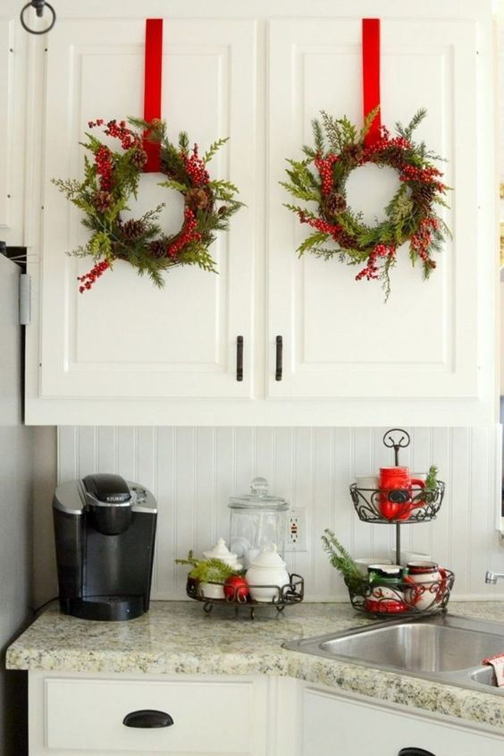 evergreen Christmas wreaths with pinecones and berries plus red ribbons for a holiday feel in the space