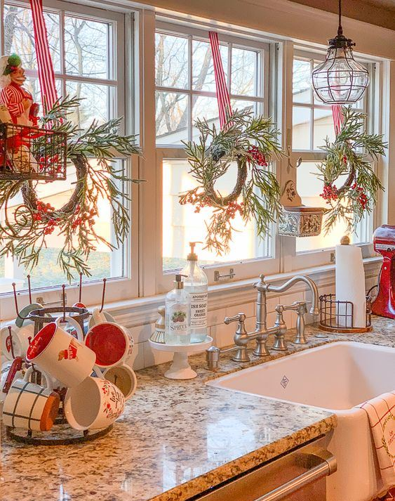 evergreen and berry Christmas wreaths, red and white mugs and striped ribbons for a holiday feel