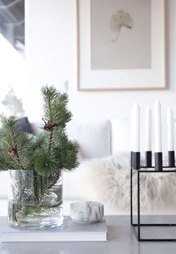 evergreen branches in a large clear vase and a modenr blakc metal candelabra with white candles for a minimal look