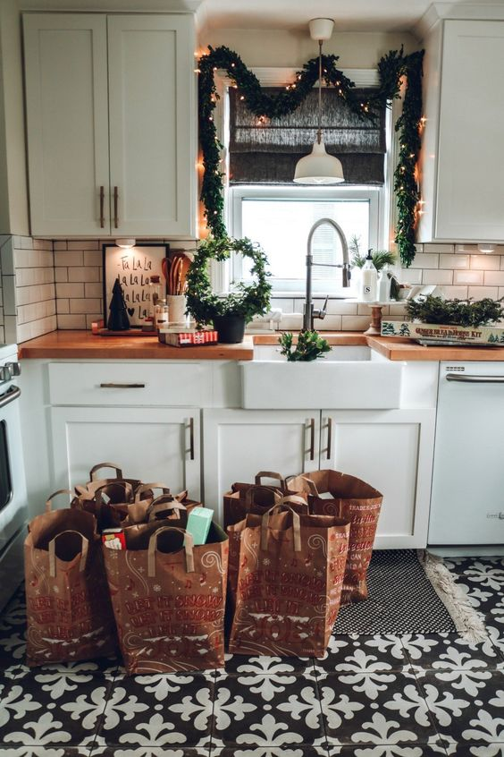 evergreen garlands with lights, a round wreath and candles for a cool and cute farmhouse Christmas kitchen