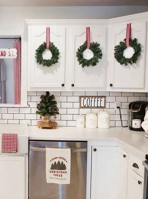 evergreen wreaths with plaid ribbons and a mini Christmas tree with red ornaments plus plaid linens