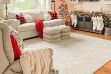 farmhouse Christmas decor with white stockings, red plaid pillows and red blankets, flocked wreaths and flocked Christmas trees plus candles
