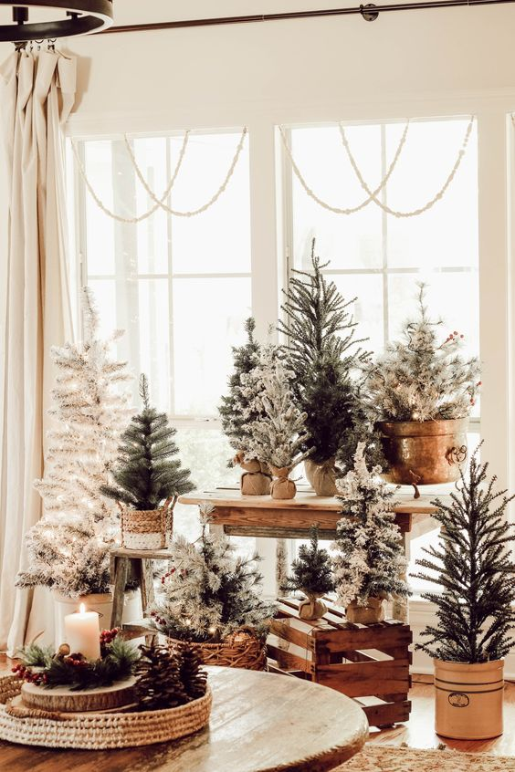 lots of usual, white and flocked Christmas trees in pots and baskets at the window will create holiday cheer easily