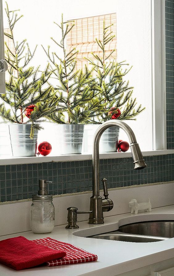 mini Christmas trees in buckets with red ornaments are all that you need for a holiday feel in the space