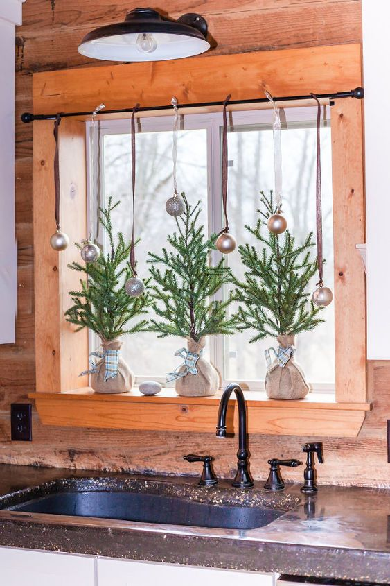 mini Christmas trees in burlap and metallic ornaments on the window for a holiday feel in the space