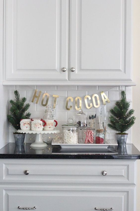 mini Christmas trees with lights, Santa mugs, sweets and gold letters for a cool and cute Christmas nook