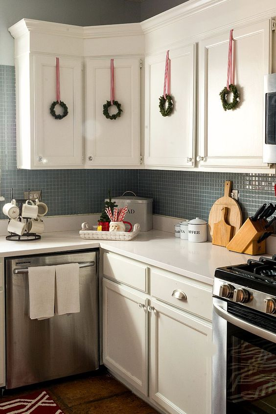mini evergreen wreaths with red ribbons hanging on cabinets look very cute and make the kitchen feel Christmas