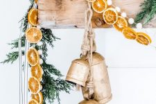 natural Christmas mantel decor with fir branches, dried citrus slices, large vintage bells and pompoms is gorgeous