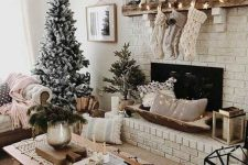 neutral knit stockings, a star garland, mini houses and candles, a greenery wreath and flocked Christmas trees