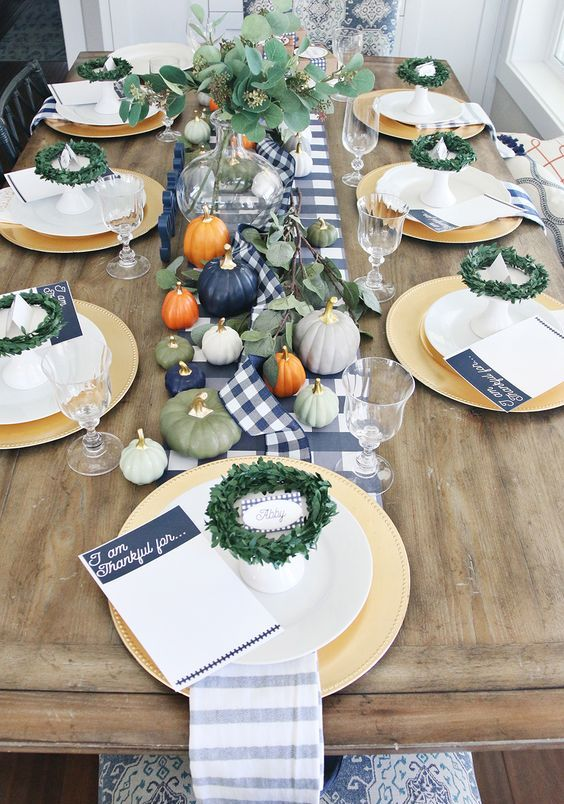 pastel pumpkins with gilded stems and greenery wreath and an arrangement for a modern Thanksgiving table