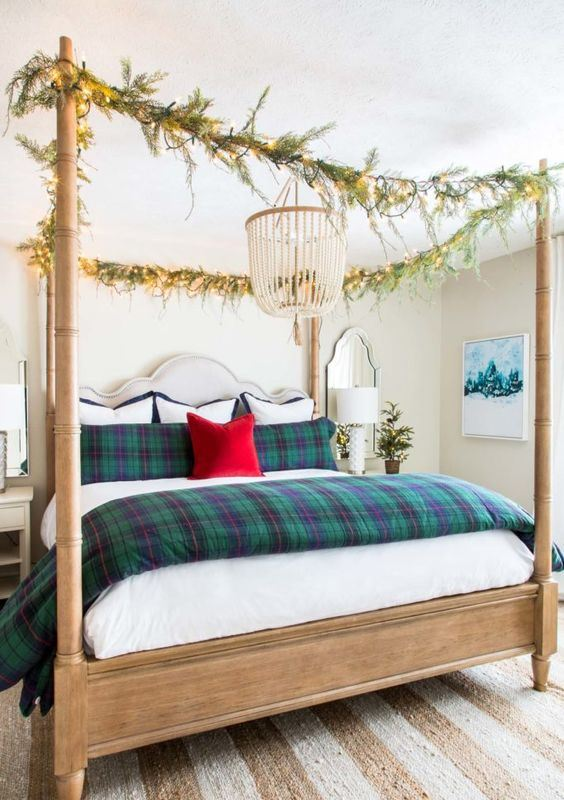 plaid bedding and evergreen and light garlands on the bed frame give a festive feel to the neutral bedroom