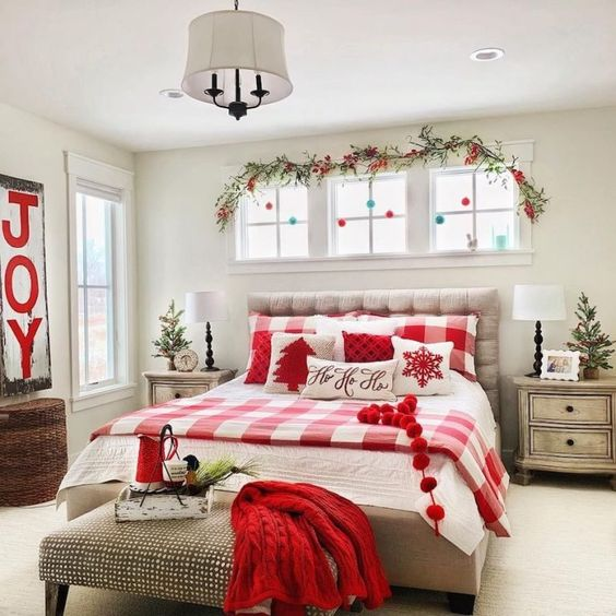 pompom garlands, an evergreen and berry branch, plaid red and white bedding and a red knit blanket for Christmas