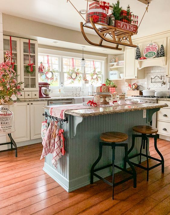 red, grey and white Christmas kitchen decor, a sleigh over the kitchen island, printed linens and a mini Christmas tree