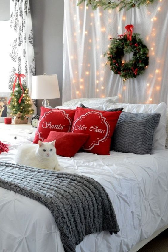 red pillows, an evergreen wreath with a red bow, lights, knit bedding and a mini Christmas tree with a red bow for a festive look