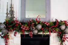 refined vintage mantel decor with greenery, plaid ribbons, oversized metal bells, vintage candleholders for Christmas