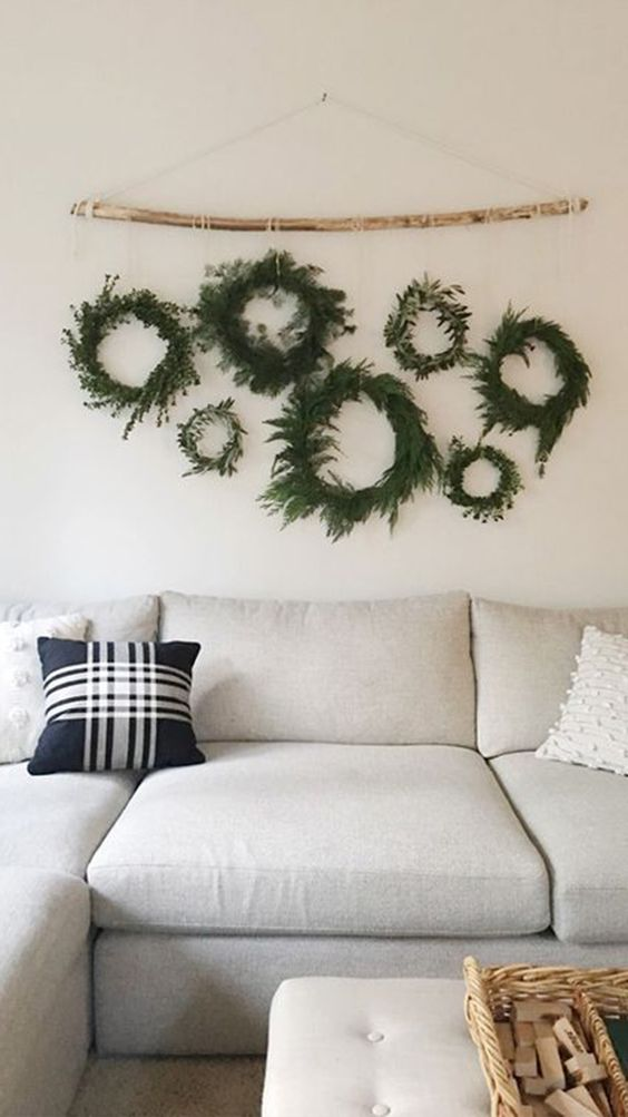 simple and natural evergreen and greenery Christmas wreaths hanging on a stick for a neutral festive touch to the space