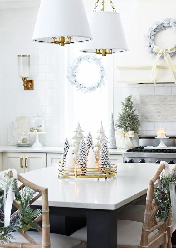 whitewashed evergreen wreaths, a mini Christmas tree, candles, ornaments and a white Christmas tree centerpiece