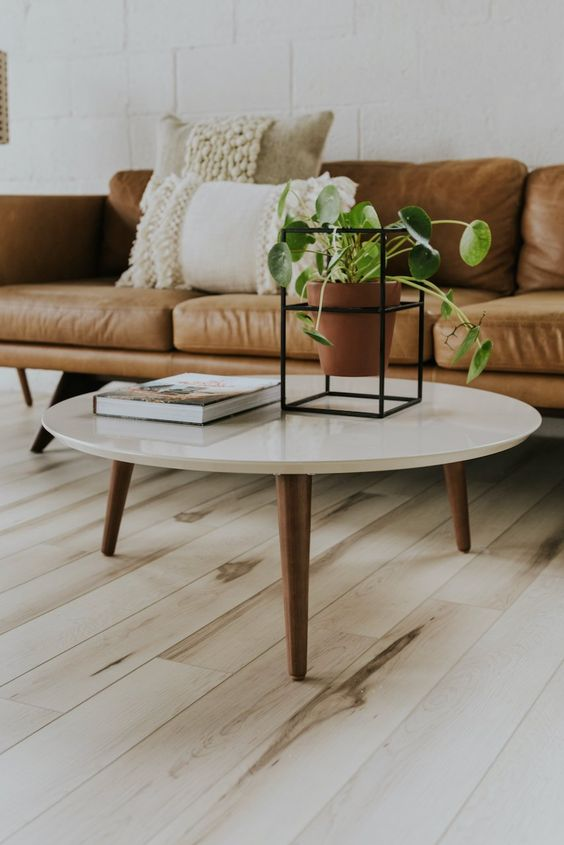 a beautiful and timeless mid-century modern coffee table with a white round tabletop and rich-stained tapered legs is a gorgeous idea to rock