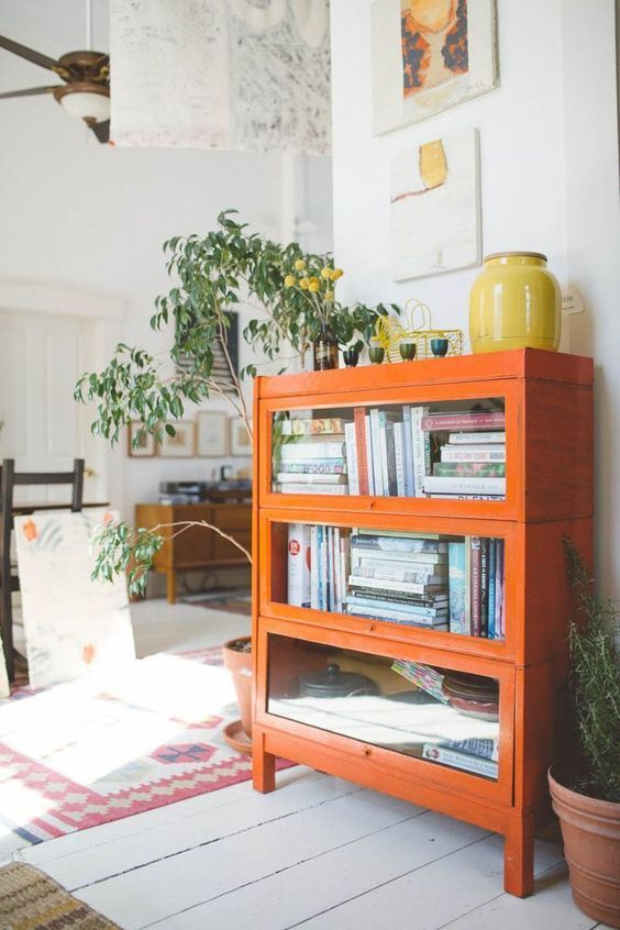 a bright orange bookcase with glass covered compartments is a great touch of color and a cute piece